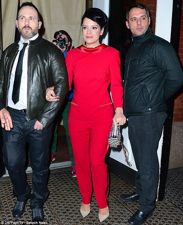 Great look: Lily opted for an all-red ensemble for the night and was pictured arriving at the party on the arm of a mystery man