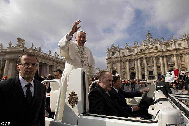 Pope Francis blesses the crowd as he arrives in St Peter's Square at the Vatican for his weekly general audience