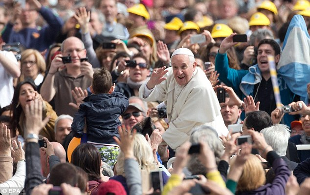 Man of the people: Pope Francis waves to a young boy in the crowds before leading his General Audience