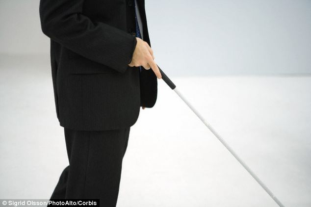 The shoes are designed for visually impaired people to be used alongside a cane (pictured) While they cannot look out for traffic like a guide dog, the shoes buzz to indicate whether a wearer should turn left or right and can lead them to their destination