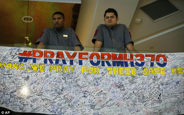 Hotel staff stand next to messages written to people affected by the missing Malaysia Airlines jetliner