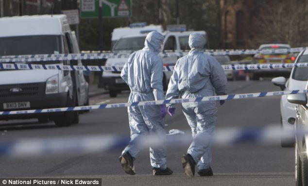 Forensic officers investigate after the 42-year-old woman was stabbed in broad daylight