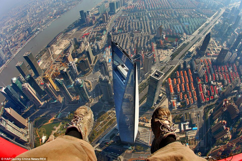 Massive drop: They could be seen dismantling the structures while donning orange helmets and yellow jumpsuits - with one even dangling his feet over the drop (above)