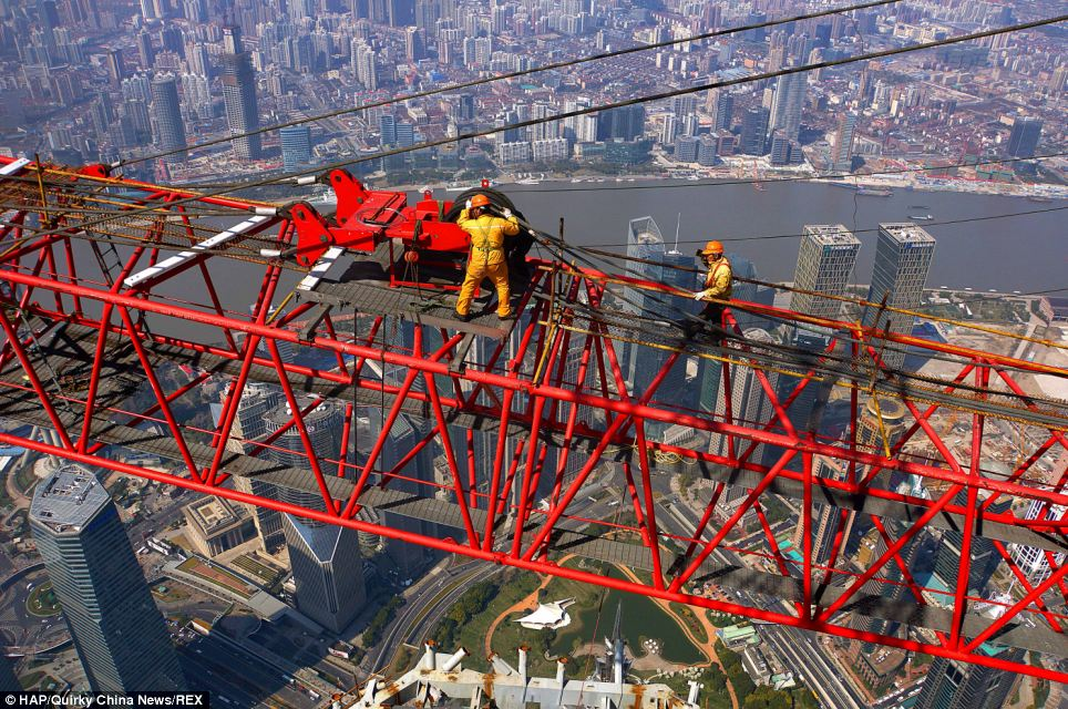 Don't look down: These construction workers show off their nerves of steel as they dismantle a crane more than 2,000ft high in Lujiazui in Shanghai's Pudong district