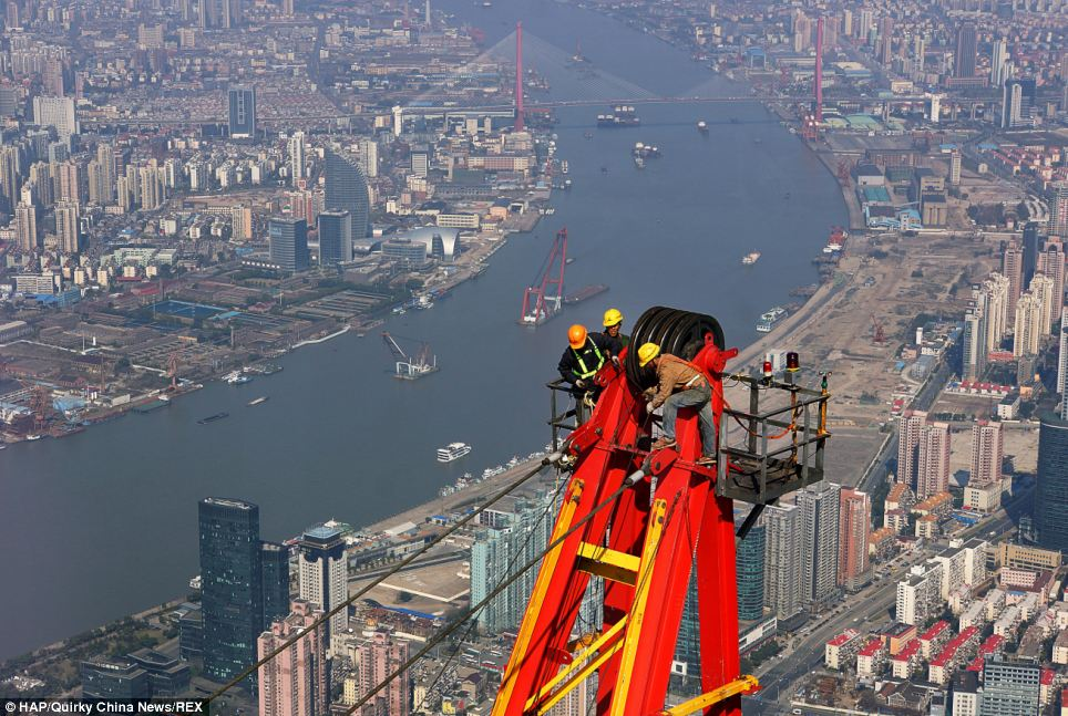 Knee-wobbling: The workers were captured standing atop cranes that helped to build the Shanghai Tower, which is China's tallest building and the world's second highest