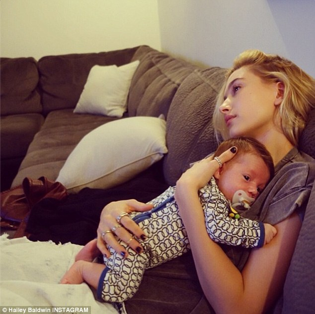 Awww: Hailey Instagrammed an image of her cuddling a baby on Thursday, while gazing wistfully off into the distance