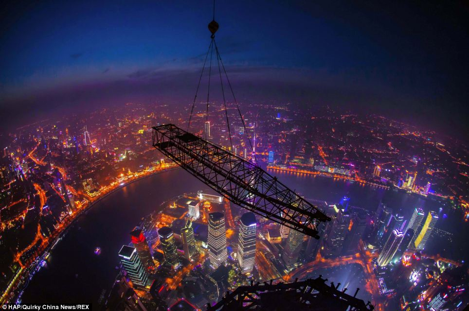 Darkness descends on the city: Workers dismantle a crane that helped to build the Shanghai Tower, the world's second highest structure after the Burj Khalifa in Dubai