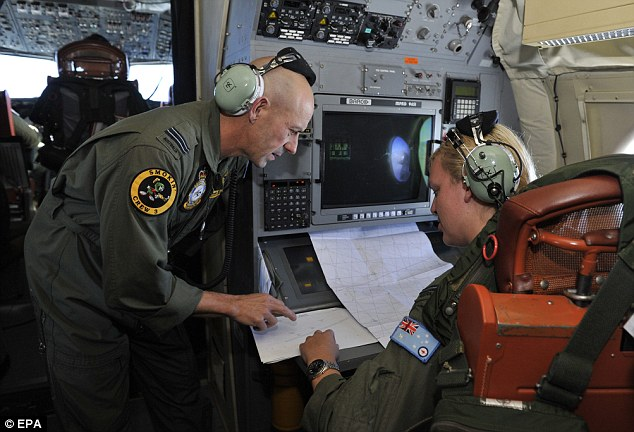 Relentless: Royal Australian Air Force crew members discuss the search area aboard the Royal Australian Airforce AP-3C Orion on Friday