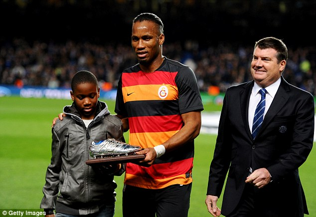 Gong fishing: Drogba, with son Isaac (L), was awarded a commemorative silver boot on his return to London
