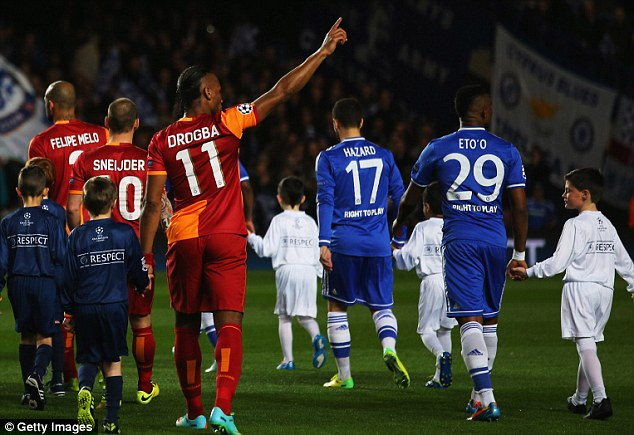 Making a point: Drogba recognises Chelsea fans while entering the pitch for the Champions League match