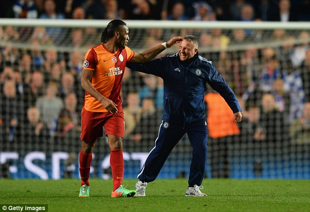 Love in: Chelsea groundsman Jason Griffin (R) finds time to give Drogba a pat on the back