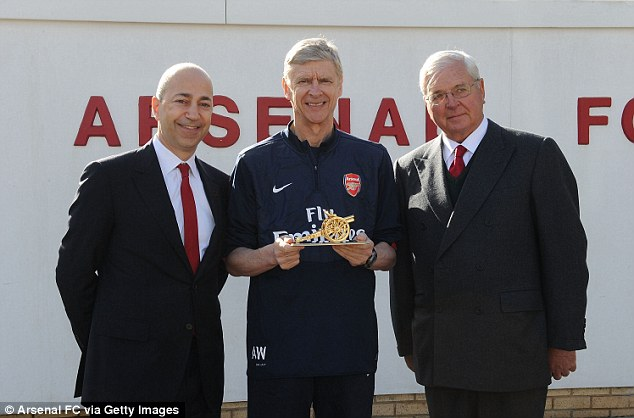 Gift: Arsene Wenger is presented with a gold canon by CEO Ivan Gazidis (left) and Chairman Sir Chips Keswick (right) to commemorate his 1000th game as Arsenal manager