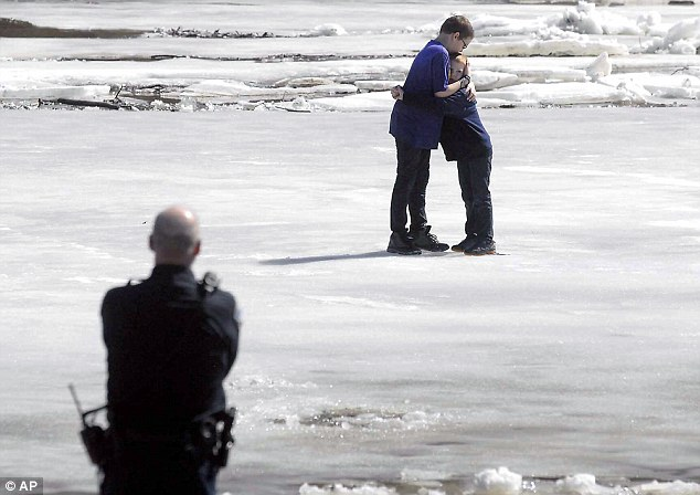 Got your back: Corbin Crawford, 12, (left) holds his brother, Dylan Crawford, 7, as they await rescue from the shifting ice on the Des Moines River in Iowa