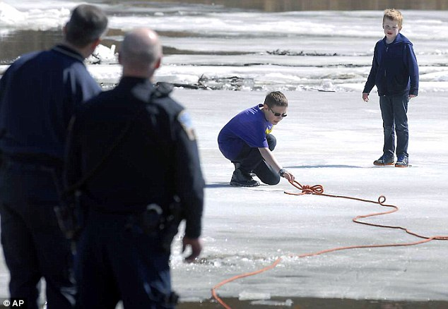 Corbin Crawford, 12, reaches out for a rope tossed to him from shore by a member of the Fort Dodge Fire Department