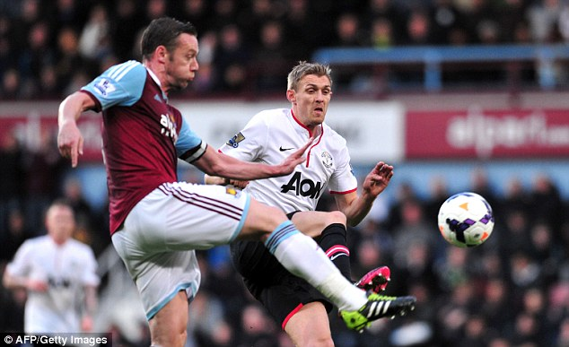 Closing down: Kevin Nolan (left) challenges Manchester United midfielder Darren Fletcher
