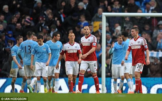 Disheartening: John Heitinga and his team-mates walk away as City celebrate another goal