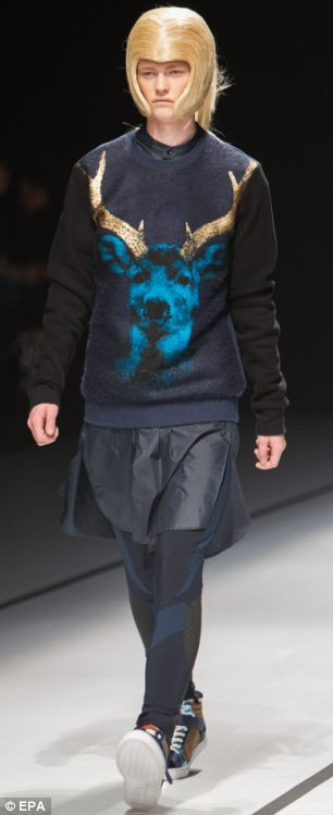 A model in a deer-inspired top and a huge blonde wig gazes at the crowd in dismay