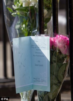 Tributes: Bunches of flowers and sympathy cards were left by visitors to the site