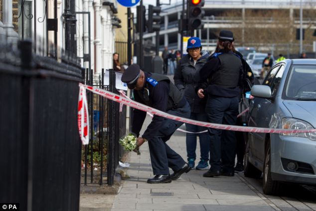 In memory: A police community support officer lays flowers handed to him by a mourner at the scene