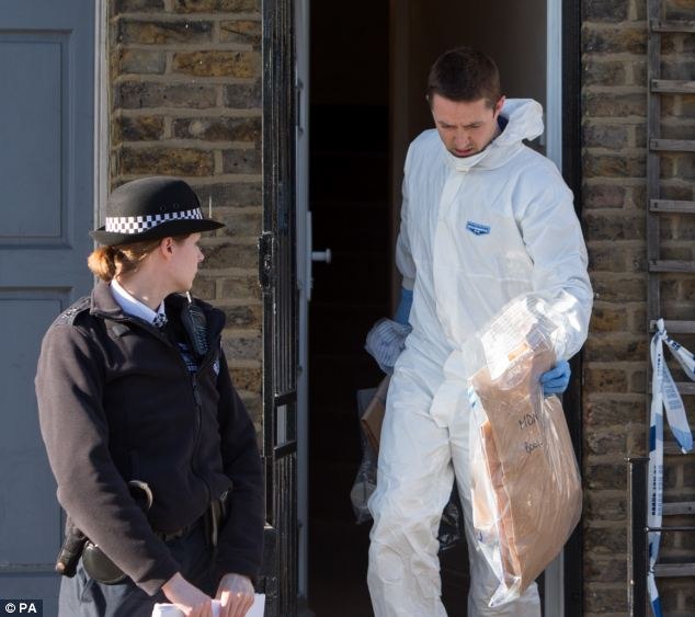 Investigation: A police forensic expert leaves the house with sealed bags of evidence