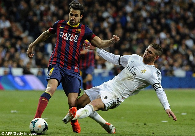 Going to ground: Ramos flies in to tackle Fabregas during the first-half of the clash