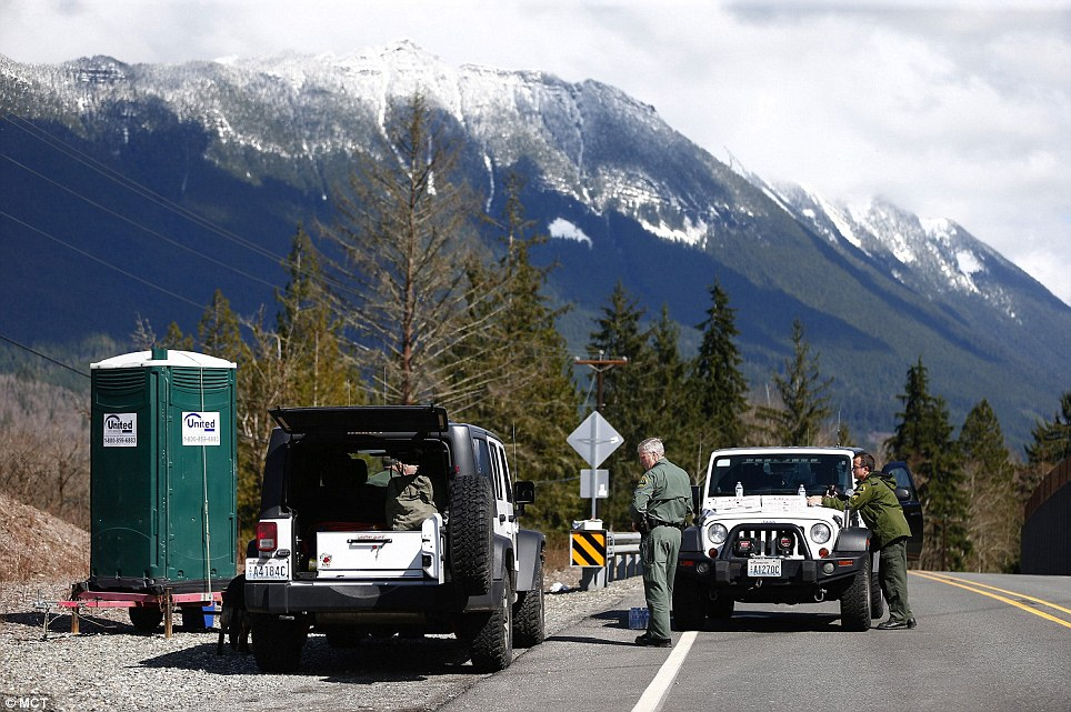 Operation: Snohomish County Sheriff officers monitor the scene along Highway 530 on Sunday close to where the mudslide took place