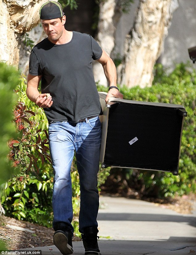 Muscle man: Josh Duhamel does some heavy lifting on Sunday to move furniture out of his Brentwood, California home