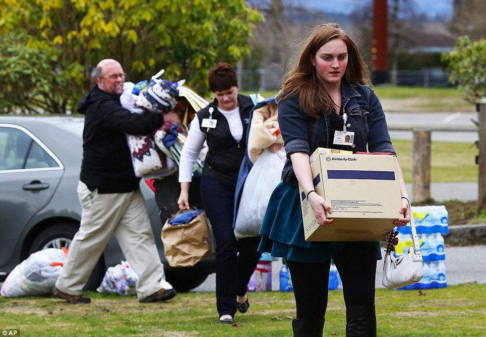 Giving what they can: Volunteers carry supplies to help set up an evacuation center at Post Middle School in Arlington to assist those impacted by the landslide