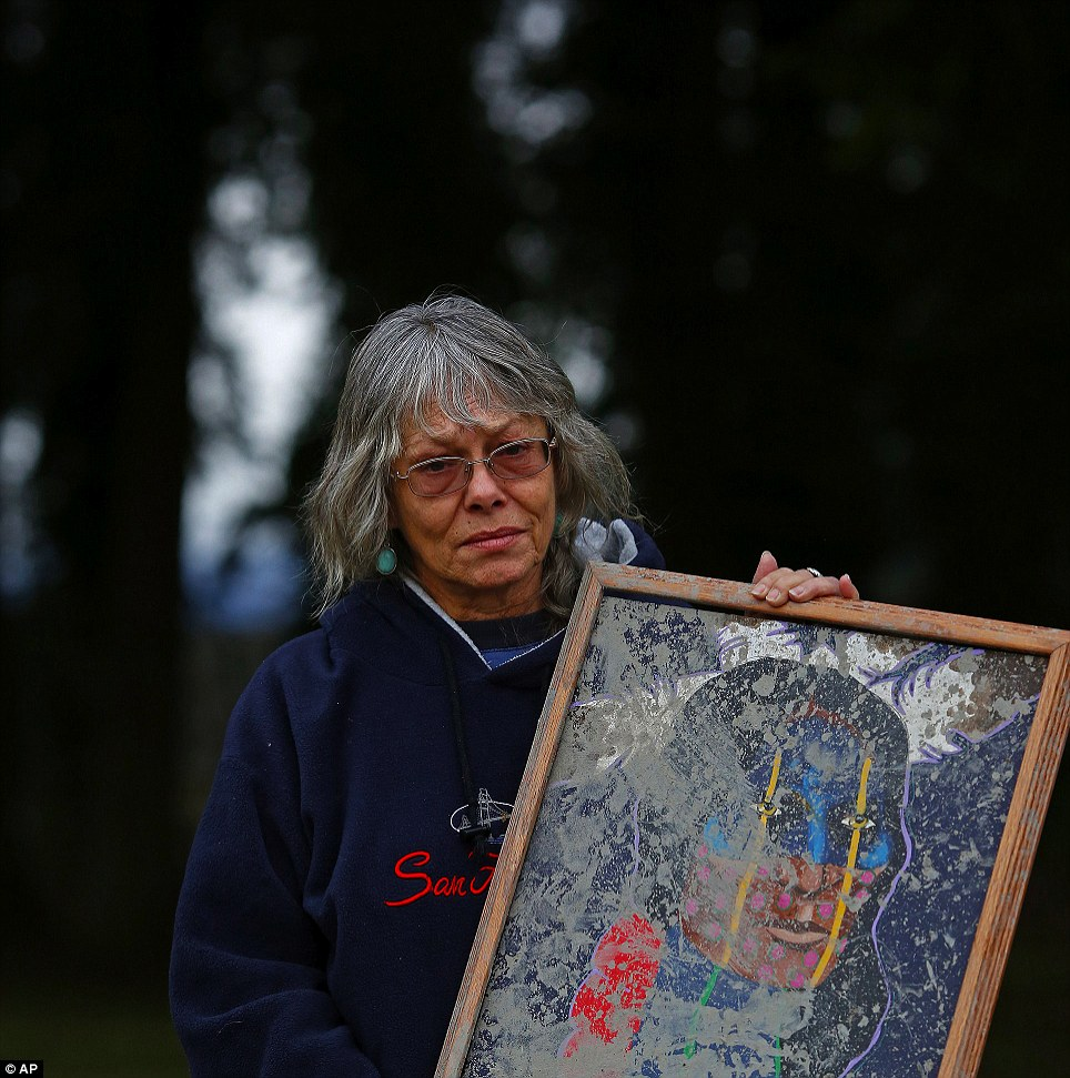 This and the clothes on her back: Robin Youngblood, who survived the landslide that destroyed her house, holds the only item that survived the disaster, a painting of a Cherokee warrior that was knocked from the wall and muddied