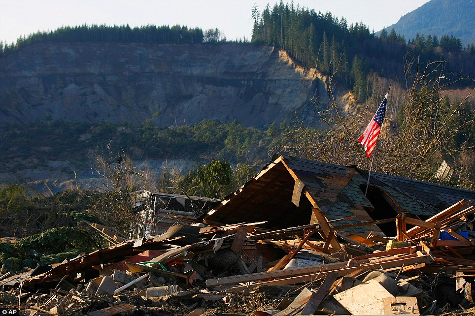 Staggering loss: A flag sits on top of what was Cory Kuntz and his family's home. The family was at a baseball game when the river of mud swept through the area and leveled their home