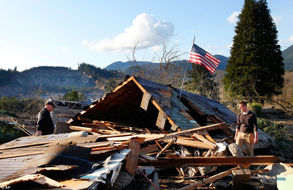 Brian Anderson, left,  and Coby Young search through the wreckage of a home belonging to the Kuntz family - who escaped certain doom while attending a Saturday morning baseball game