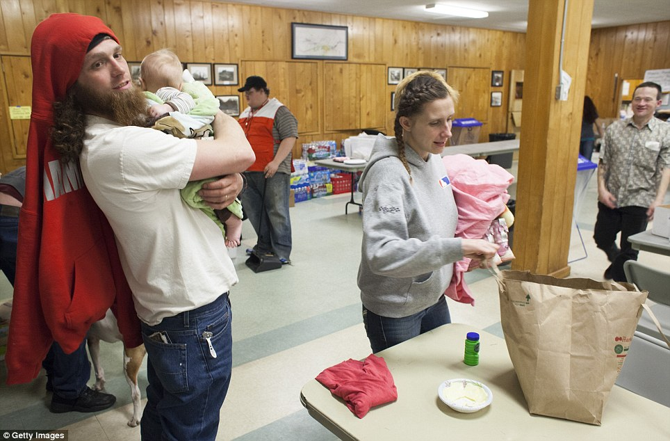 Temporary relief: Kristopher Langton (left) is pictured holding his five-month-old son Kristian Langton after eating dinner with wife LoAnna Langton (right) at a temporary Red Cross shelter at the Darrington Community Center in Darrington, Washington