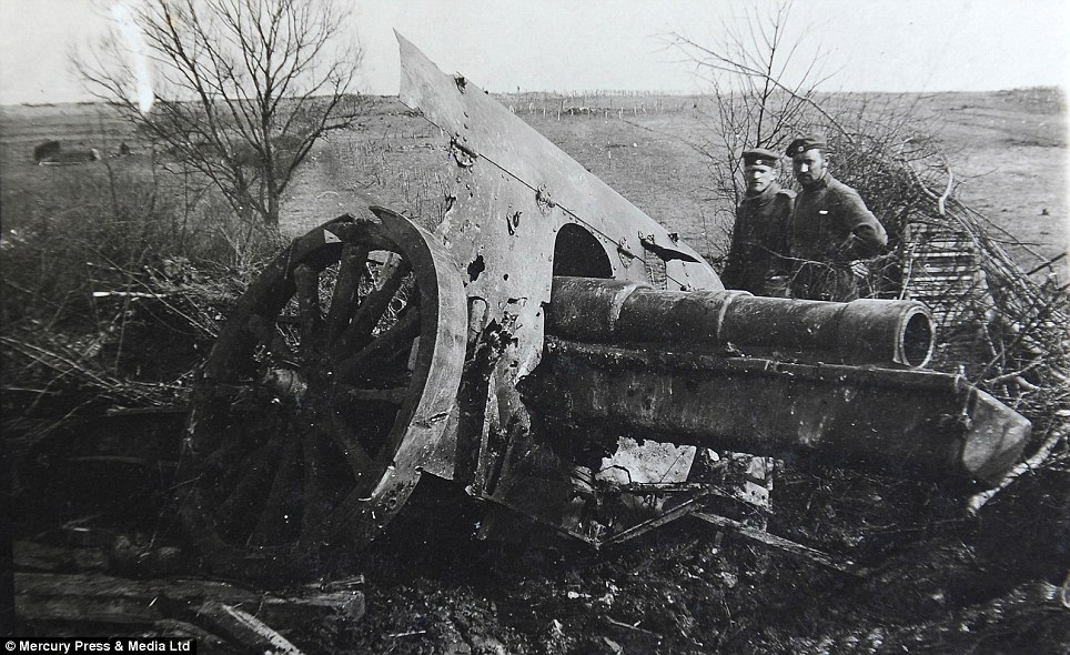 Destroyed: Two men stand next to a damaged cannon which had sunk into the mud of the European battlefield