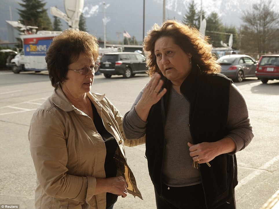 Pain: Brenda Neal (R) is consoled by Carol Massingale after looking at aerial posted photos of a massive landslide for her missing husband in Darrington, Washington March 24, 2014