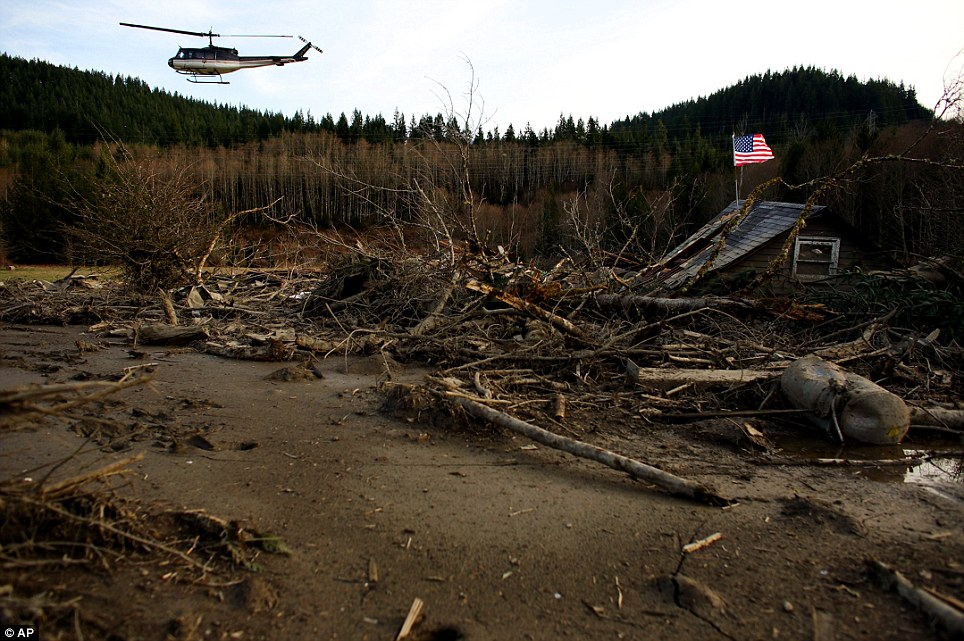 Search: From a helicopter, Snohomish County Sheriff Ty Trenary surveys the wreckage of homes destroyed in Saturday's mudslide near Oso, Washington as the search for survivors grew on Monday to include scores of people who were still unaccounted for