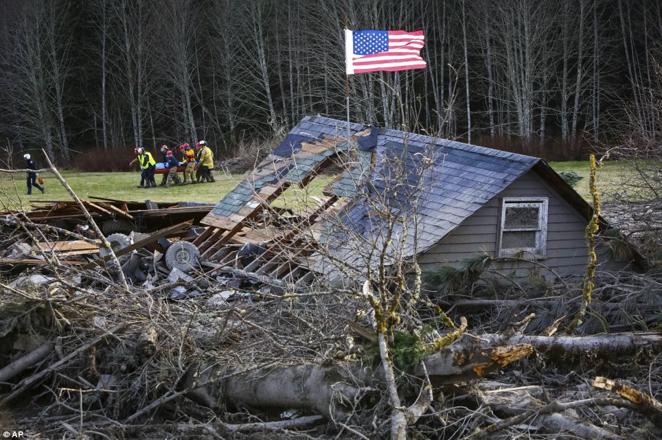 Here rescue workers are seen removing a body from the wreckage of homes destroyed by a mudslide near Oso