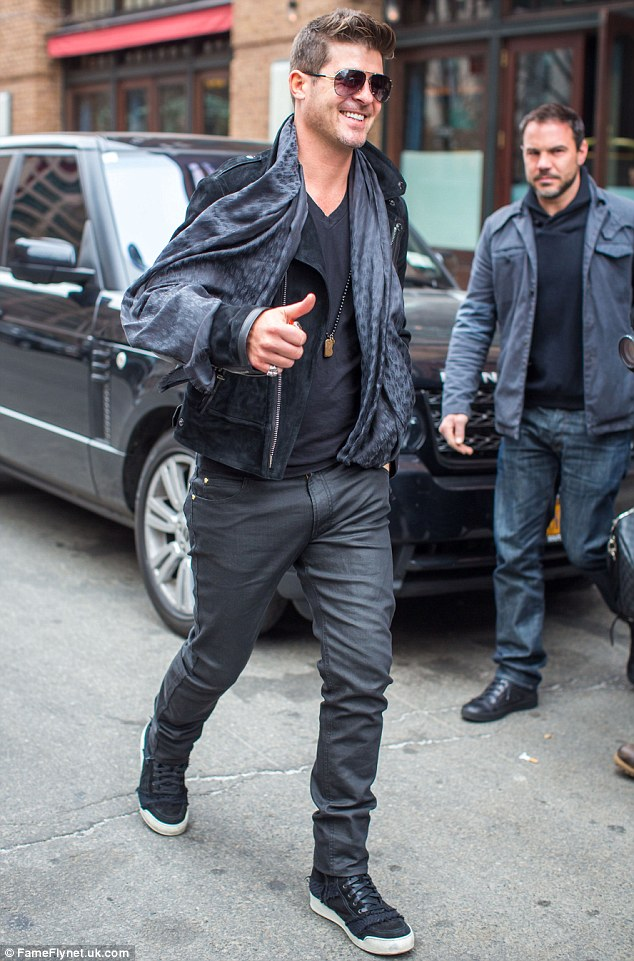 Acting natural? Robin Thicke smiled from ear to ear as he gave the thumbs up on the way out of his New York City hotel on Tuesday all dressed up in swanky gear