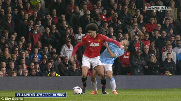 Lucky boy: Marouane Fellaini was fortunate to escape with just a yellow card after appearing to elbow Pablo Zabaleta in full view of the referee