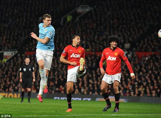 Caught out: Rio Ferdinand and Marouane Fellaini are left flat-footed as Edin Dzeko puts City two goals ahead