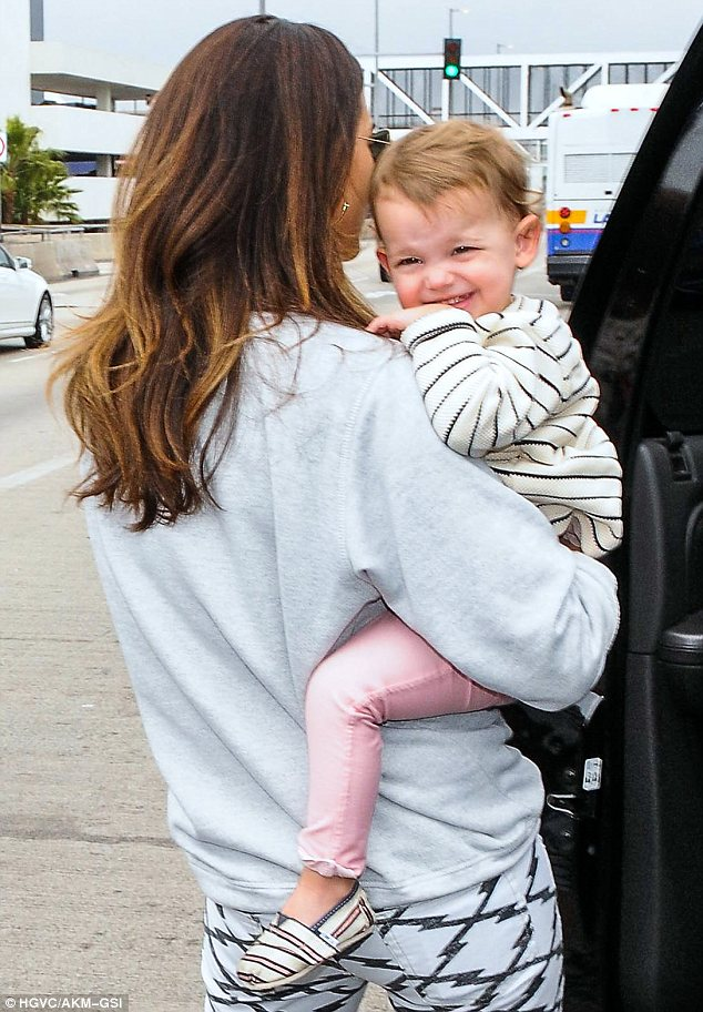 Future star: Dixie flashed a huge smile as she was carried in to LAX by her mother
