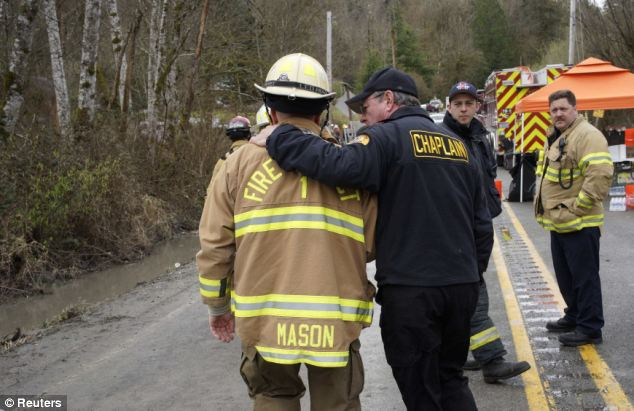 Sadness: Snohomish County Fire Chief Steve Mason (left) talks with a chaplain near the mudslide near Oso, Washington as efforts continued to find victims. The death toll now stands at 24