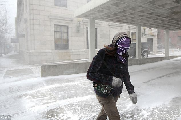 Keeping covered: A woman in New Bedford, Massachusetts hides her face as she ventures outdoors