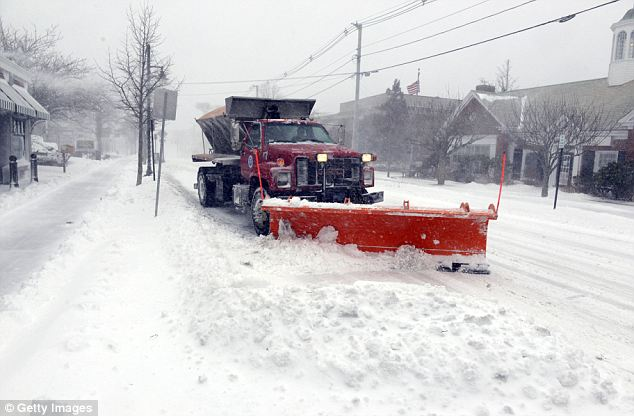 Make way: A snow plow goes down Main Street in Hyannis as authorities warned residents to avoid going outdoors