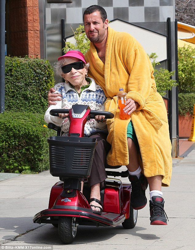 Hitching a ride: Adam Sandler films scenes for a new movie while perched on the red mobility scooter which was being driven by an elderly woman