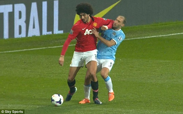 Making contact: Fellaini's elbow clouts Zabaleta in the jaw as the Argentine goes to ground