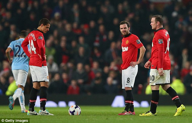 Bad times: Javier Hernandez, Juan Mata and Wayne Rooney stand around dejected after Manchester City score the third of their goals in Tuesday's 3-0 derby win at Old Trafford