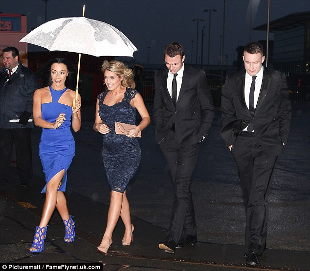 Black and blue: Kaya held an umbrella over herself and pregnant Helen as their respective men followed close behind