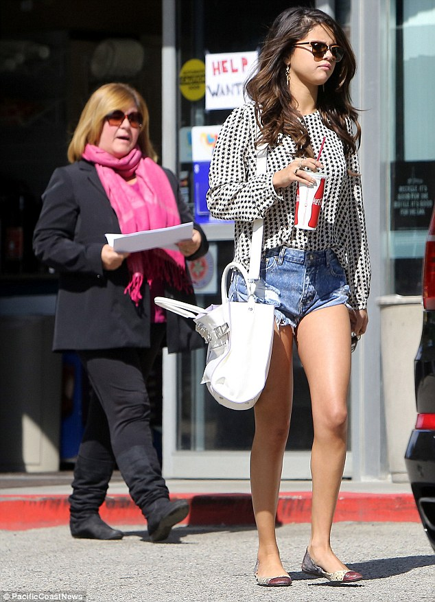 Legal papers: Selena was seen being approached by a woman in a pink scarf and handed some documents after allegedly being subpoenaed to testify in her on/off boyfriend Justin Bieber's photographer lawsuit