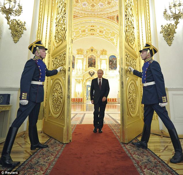 Golden gates: Meanwhile, Russia's President Vladimir Putin attends a meeting with the newly promoted top officers from various branches of the Russian armed forces and Interior Ministry at the Kremlin in Moscow