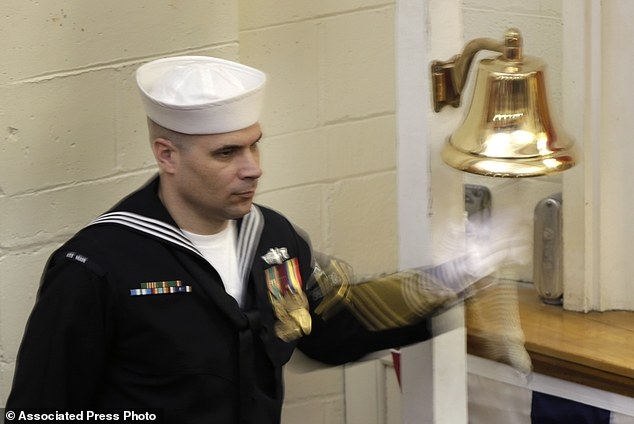 Final farewell: A sailor rings a bell at the conclusion of the  decommissioning ceremony